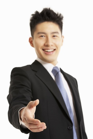 welcoming: Studio Portrait Of Chinese Businessman Reaching Out To Shake Hands