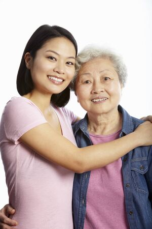 grown ups: Studio Portrait Of Chinese Mother With Adult Daughter Stock Photo