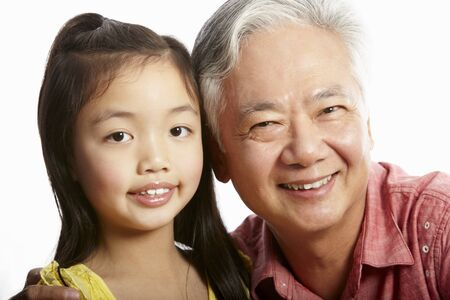 Studio Shot Of Chinese Grandfather With Granddaughter photo