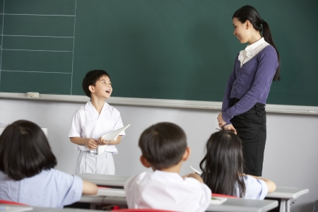 Pupil And Teacher Standing By Blackboard In Chinese School Classroom photo