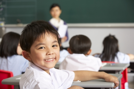 school year: Portrait Of Male Pupil Working At Desk In Chinese School Classroom Stock Photo