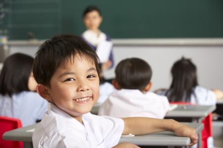 mujer hijos: Retrato De Estudiante Masculino Que Trabaja En El Escritorio En Aula Escuela China Foto de archivo