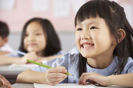 ni�os en la escuela: Grupo de estudiantes que trabajan en pupitres En Aula Escuela China Foto de archivo