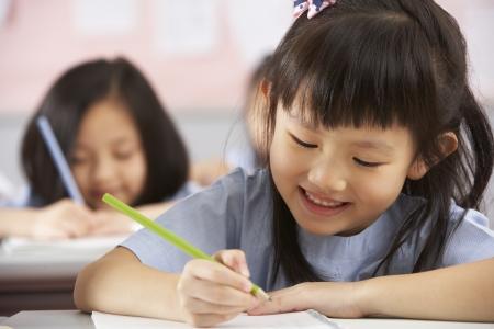 escuela primaria: Grupo de estudiantes que trabajan en pupitres En Aula Escuela China Foto de archivo