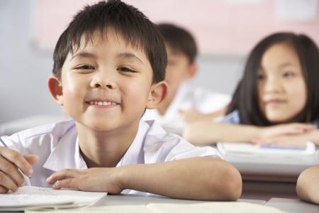 ni�as chinas: Grupo de estudiantes que trabajan en pupitres En Aula Escuela China Foto de archivo