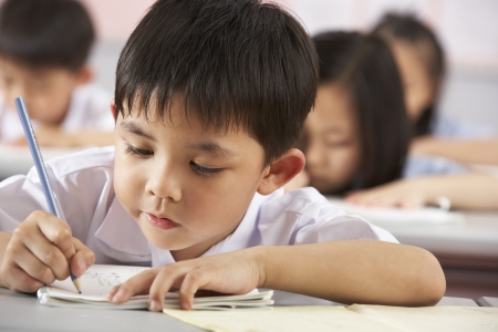 6 year old children: Group Of Students Working At Desks In Chinese School Classroom