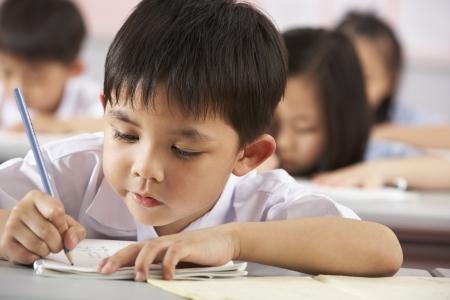 uniforme escolar: Grupo de estudiantes que trabajan en pupitres En Aula Escuela China Foto de archivo