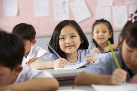 Group Of Students Working At Desks In Chinese School Classroom photo