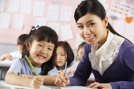 classroom teacher: Allievo d'aiuto lavora alla scrivania in Scuola Aula cinese