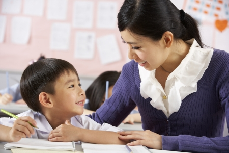 Teacher Helping Student Working At Desk In Chinese School Classroom photo