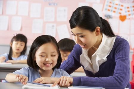 niños estudiando: Maestros Ayudando a Estudiantes Trabajando En El Escritorio En Aula Escuela China Foto de archivo