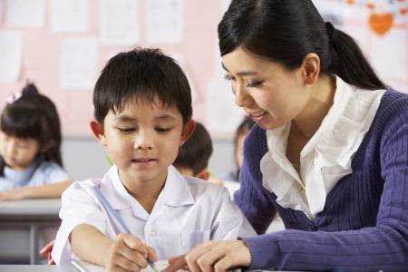 ni�os sentados: Maestros Ayudando a Estudiantes Trabajando En El Escritorio En Aula Escuela China Foto de archivo
