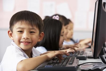 escuela primaria: Pupila masculina Uso del teclado de ordenador Durante la Clase A Aula Escuela China