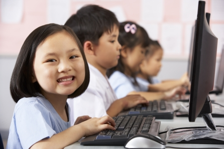 6 year old children: Female Pupil Using Keyboard During Computer Class In Chinese School Classroom