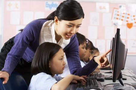 asian teacher: Teacher Helping Student During Computer Class In Chinese School Classroom