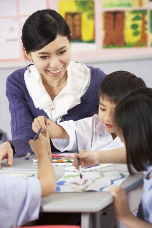 school teacher: Teacher Helping Students During Art Class In Chinese School Classroom