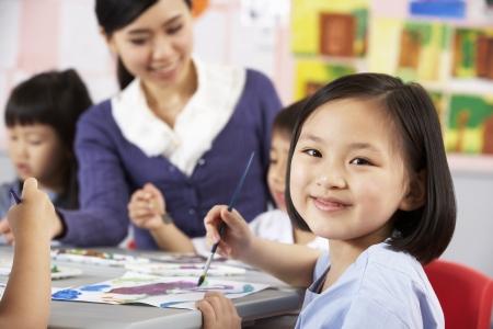 asia children: Female Pupil Enjoying Art Class In Chinese School Classroom Stock Photo