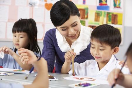 asian teacher: Teacher Helping Students During Art Class In Chinese School Classroom