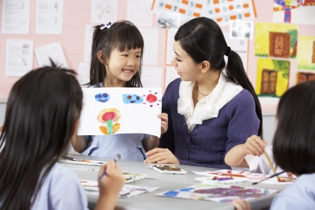 four classes: Teacher Helping Students During Art Class In Chinese School Classroom