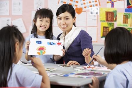 escuela primaria: Maestros Ayudando a los Estudiantes Durante la clase de arte en la Escuela Aula chino