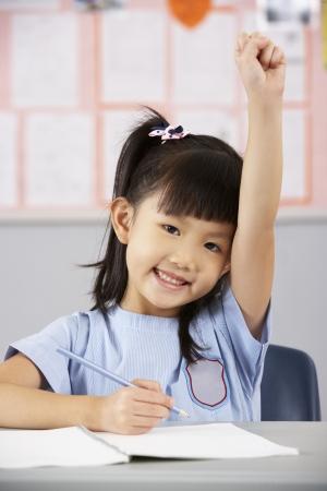 preguntando: Estudiante Femenino Que Trabaja En El Escritorio En Aula Escuela China