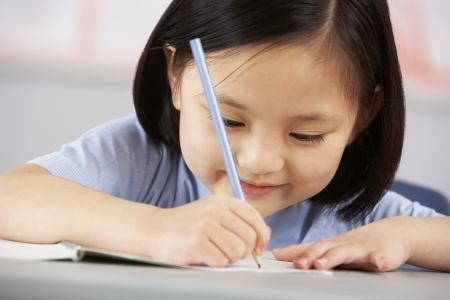 child learning: Female Student Working At Desk In Chinese School Classroom
