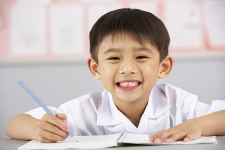 Male Student Working At Desk In Chinese School Classroom Stock Photo - 18709439