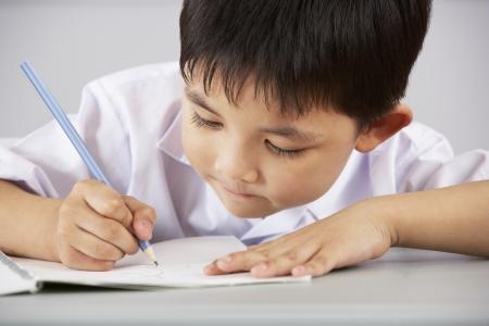 niños estudiando: Estudiante Masculino Que Trabaja En El Escritorio En Aula Escuela China Foto de archivo