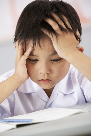 struggling: Unhappy Male Student Working At Desk In Chinese School Classroom