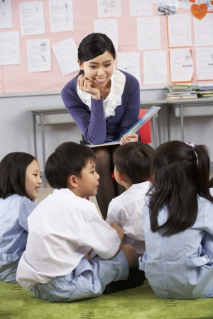 asian teacher: Teacher Reading To Students In Chinese School Classroom