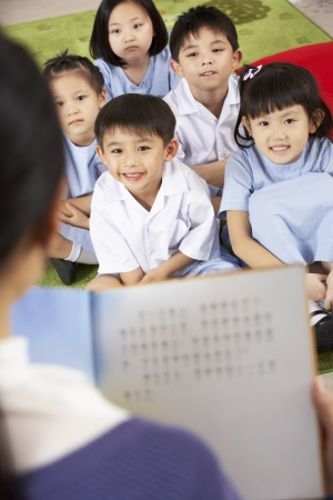 Teacher Reading To Students In Chinese School Classroom photo