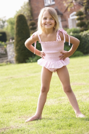 Portrait Of Young Girl Standing In Garden Wearing Swimming Costume photo
