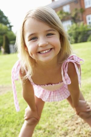 enfant maillot: Portrait de jeune fille debout dans le jardin en costume de bain