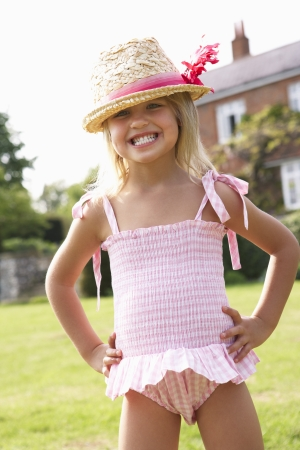 child swimsuit: Portrait Of Young Girl Standing In Garden Wearing Swimming Costume