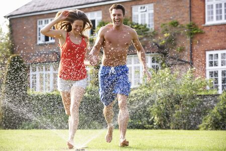 sprinkler: Couple Running Through Garden Sprinkler