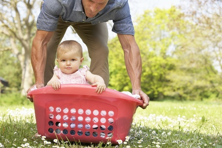 man laundry: Father Carrying Baby Girl Sitting In Laundry Basket Stock Photo