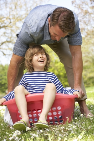 Father Carrying Son Sitting In Laundry Basket photo