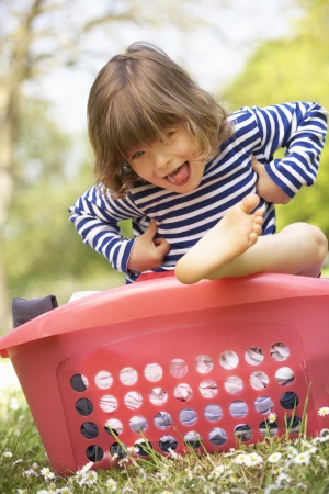 Young Boy Sitting In Laundry Basket Stock Photo - 18710138