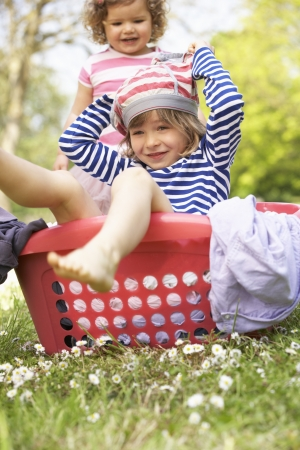 Young Boy Sitting In Laundry Basket photo