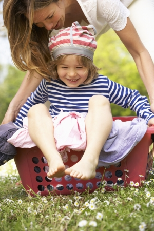 Mother Carrying Son Sitting In Laundry Basket photo