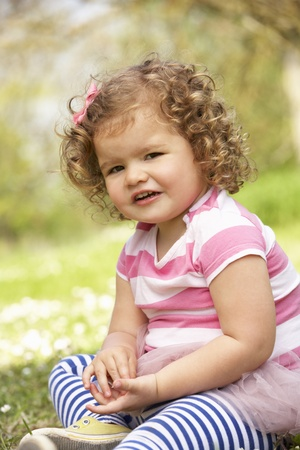 1 year old: Young Girl In Summer Dress Sitting In Field