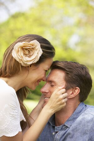Romantic Couple Sitting In Field Of Summer Flowers photo