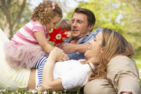 Parents Sitting With Children In Field Of Summer Flowers photo
