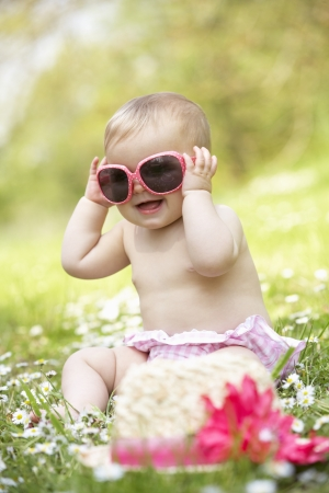 Baby Girl In Summer Dress Sitting In Field Wearing Sunglasses photo