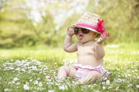 フィールドの身に着けているサングラスと麦わら帽子座っている夏のドレスの赤ちゃん