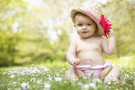 straw hat: Neonata in vestito da estate seduta in campo indossare occhiali da sole e cappello di paglia