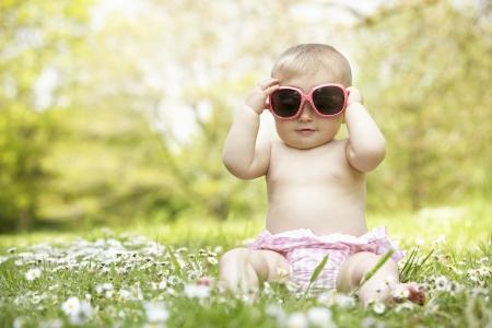 flowery: Baby Girl en el vestido de verano que se sienta en campo con gafas de sol Foto de archivo