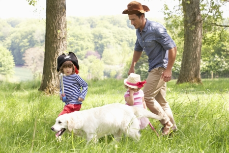 person outside: Father Playing Exciting Adventure Game With Children And Dog In Summer Field Stock Photo