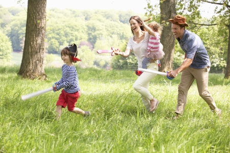 happy children: Parents Playing Exciting Adventure Game With Children In Summer Field