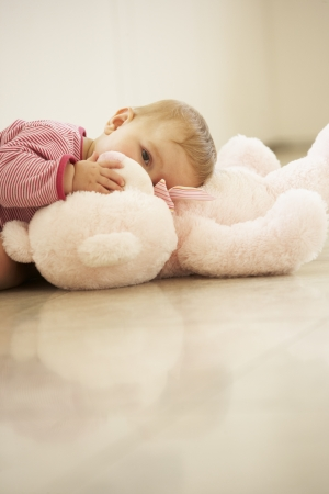 Baby Girl Cuddling Pink Teddy Bear At Home photo